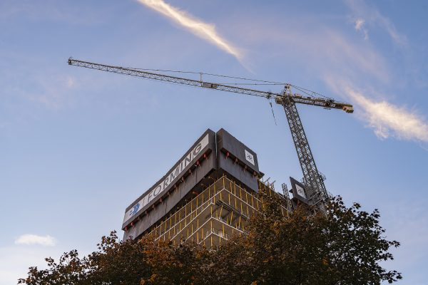 Looking up at One Richmond Row as if emerging from the tree tops along with the crane at sunset
